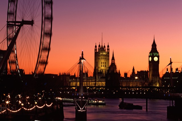 London skyline at sunset including the London Eye, Hungerford Foot Bridge and the Houses of Parliament